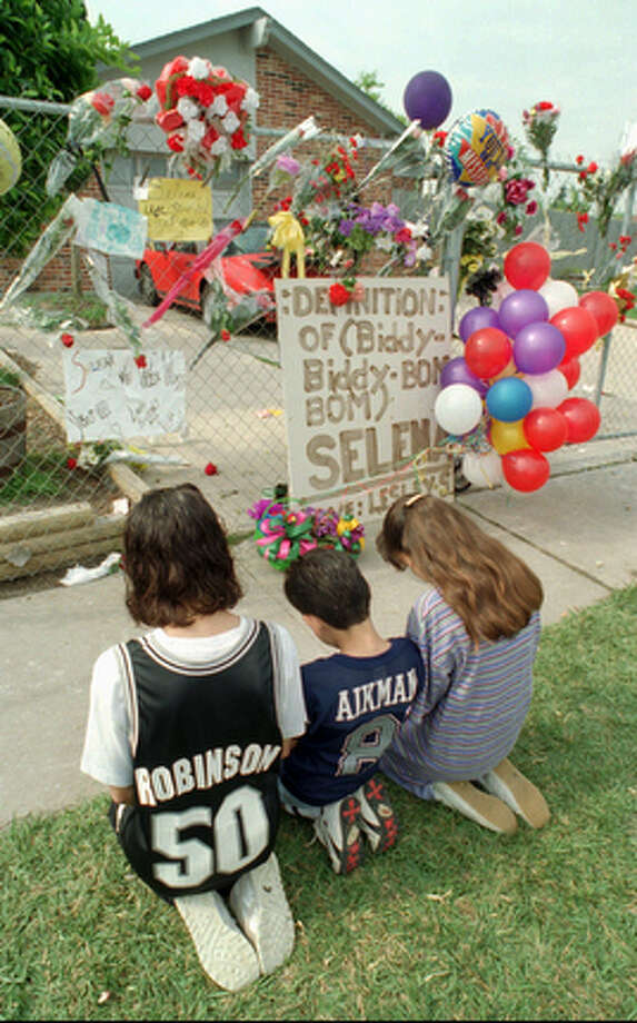 A trio of young mourners kneel and pray outside the home of slain Tejano singer Selena Quintanilla Perez the day after her death April 1, 1995, in Corpus Christi, Texas. / AP1995