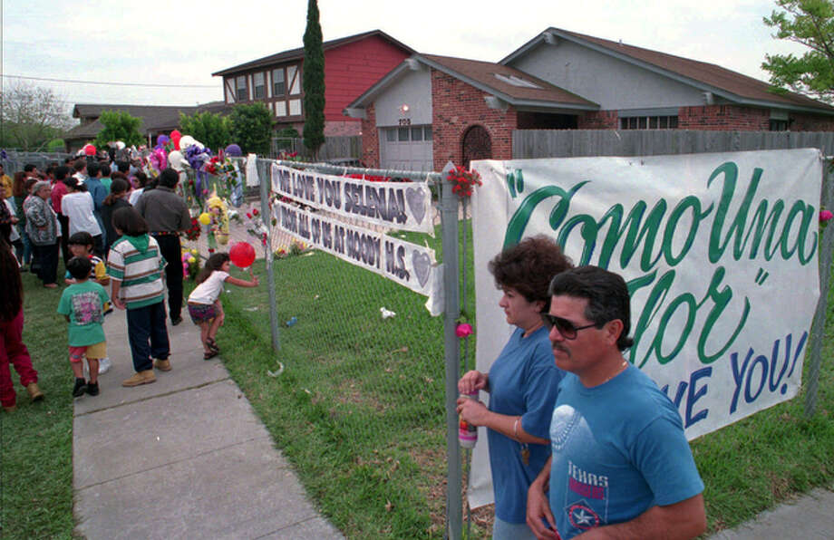 Neighbors from the Molino neighborhood pass by a sign put up for Selena on their way to visit her house on April 1, 1995