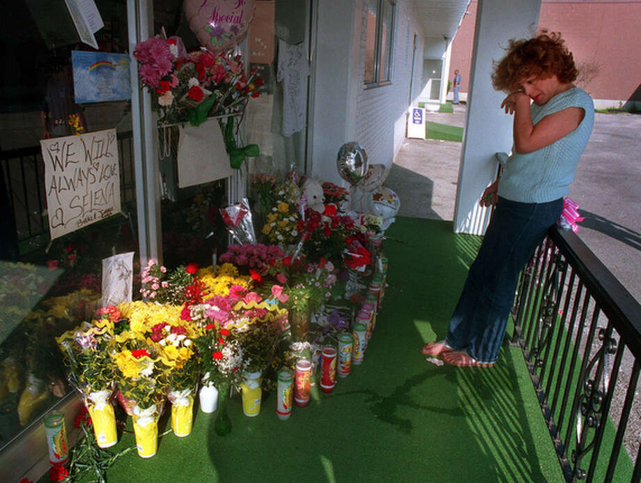 Gina Amaya (front) and Yvonne Martinez bring a small bouquet of flowers to lay at the front door of the Selena boutique on Broadway on March 31, 1995  afternoon after learning of the singer's death.