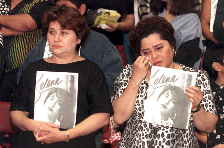 Estella Leak, right, wipes away tears during a memorial tribute for the slain Grammy-winning pop star Selena on April 2, 1995 at the Los Angeles Sports Arena.   On the left is Estella Leak's sister, Olivia. / AFP