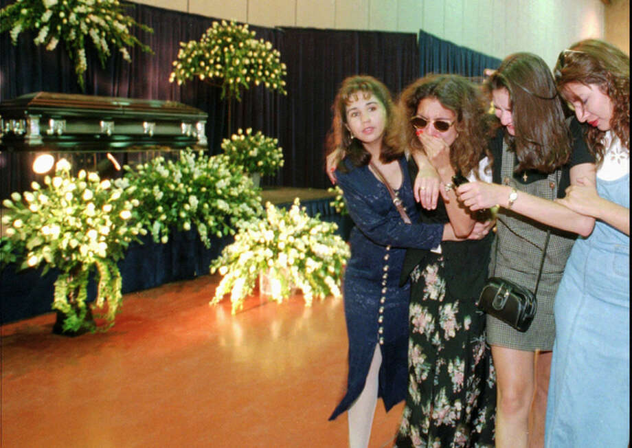 Fans of slain Grammy-winning singer Selena, from right, Amanda Gomez, Nency Gonzales, Dorisa Rivera and Luann Mora, comfort one another as they pass by the casket of the slain singer during a service Sunday, April 2, 1995, in Corpus Christi. / AP1995