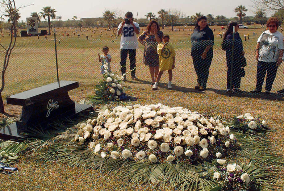 Visitors to grave of slain Tejano music star Selena stop to pay their respects and take photographs on Saturday, March 30, 1996, in Corpus Christi. / AP1996