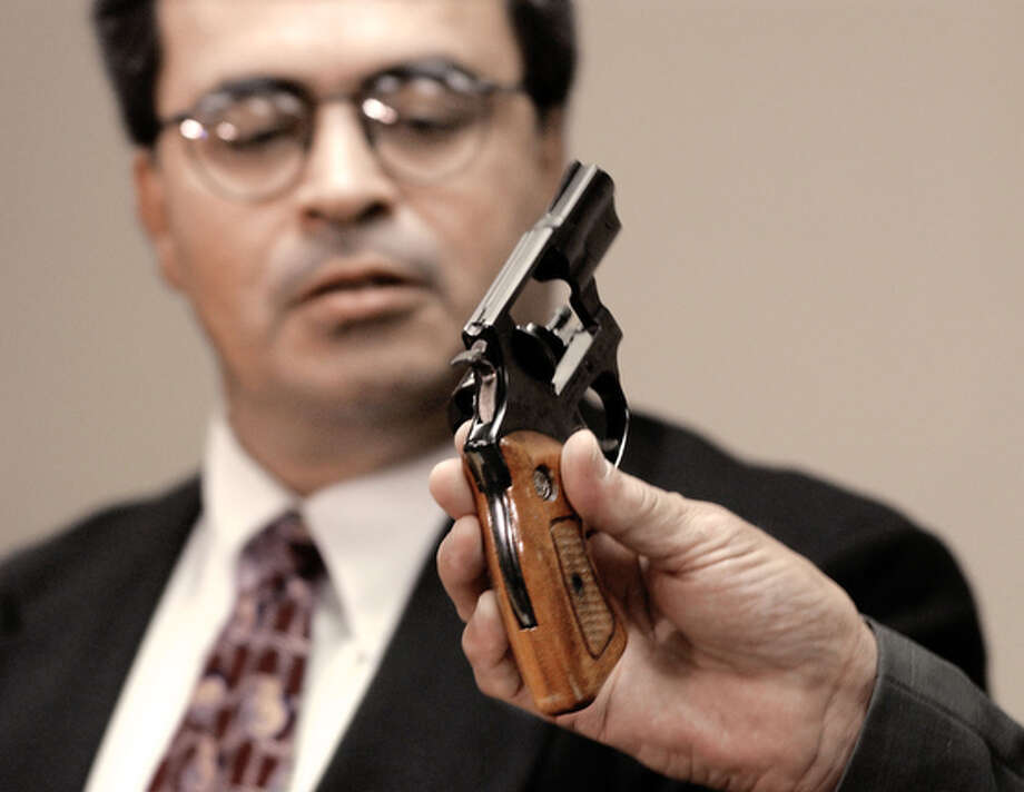 Corpus Christi Texas District Attorney Carlos Valdez, left,  examines a .38-caliber Taurus revolver that only fired one shot, the one that killed the singer Selena, Friday, May 31, 2002, during a news conference in Corpus Christi. / CORPUS CHRISTI CALLER-TIMES