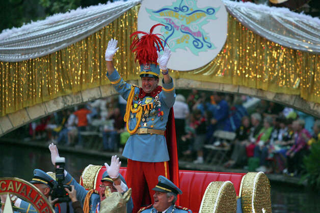 King Antonio Nick Campbell waves to the crowd Monday night during the Texas Cavaliers River Parade. The theme of this year's parade was River of Dreams. / jdavenport@express-news.net