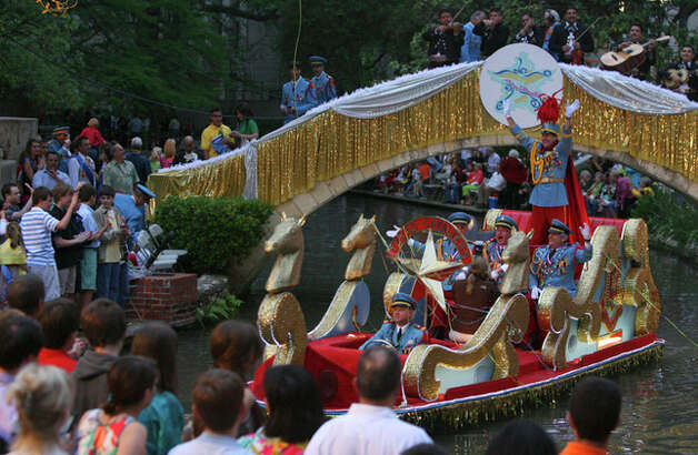 King Antonio's float enters the Arneson River Theater area Monday night during the Texas Cavaliers River Parade. Standing on the back of the float waving his arms is the 88th King Antonio, Nick Campbell. / jdavenport@express-news.net