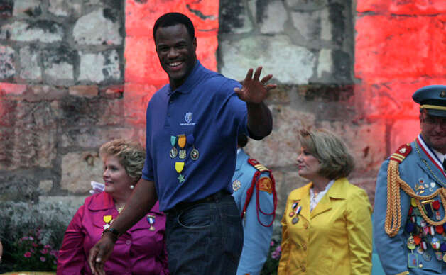 Spurs great David Robinson, grand marshal of the Texas Cavaliers River Parade, waves to the crowd at the River Parade Monday. / jdavenport@express-news.net