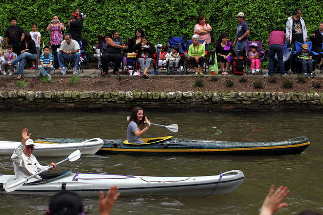 Kayakers wave at spectators from the river. / spoecial to the San Antonio Express-News