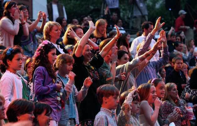 The crowd waves as barges pass at Arneson Theater. / jdavenport@express-news.net