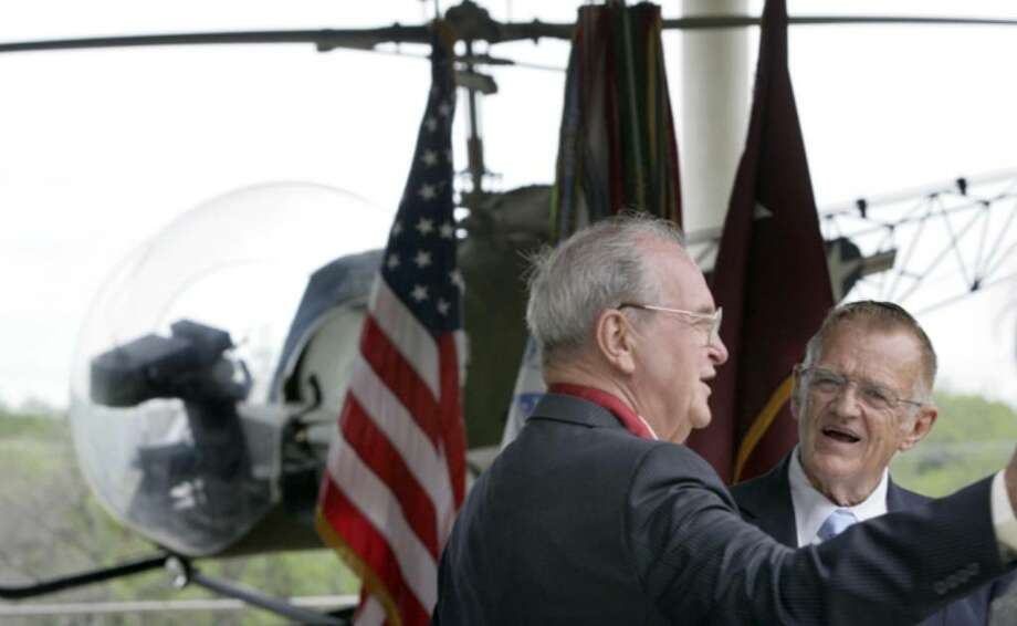 Solopilot William A. Bush (left) shares war stories with retired Command Sgt. Maj. James Hardin in front of an H-13 medical helicopter during a ceremony honoring solopilots at Fort Sam Houston.