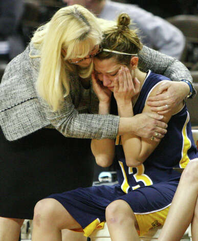 Poth's head coach Peggy Hosek hugs player Erica Moczygemba near the end of the game. / eaornelas@express-news.net