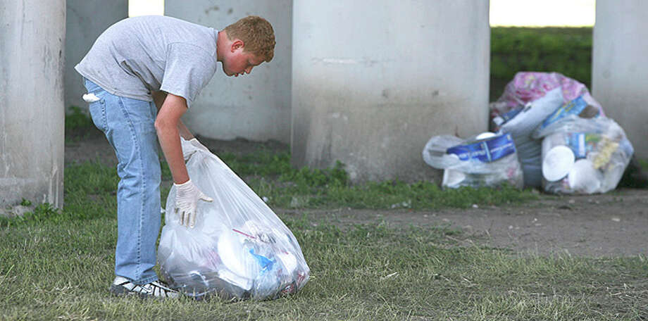 Christian Cook,13, picks up trash under the freeway overpass near Broadway the morning after the Fiesta Flambeau parade. Cook said he was picking up trash for his grandmother Mary Ann Hill, who owns the nearby Pig Stand restaurant. / John Davenport/Express-News