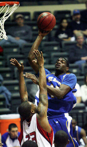 Jeremy Fonteneaux gets up for a short jumper against UIW's Deleon Hines. / © 2010 San Antonio Express-News