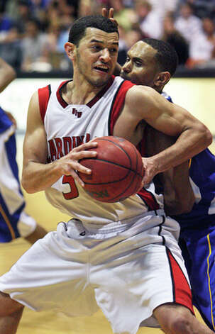 UIW's Pierce Caldwell is checked closely by Darren Lee. / © 2010 San Antonio Express-News