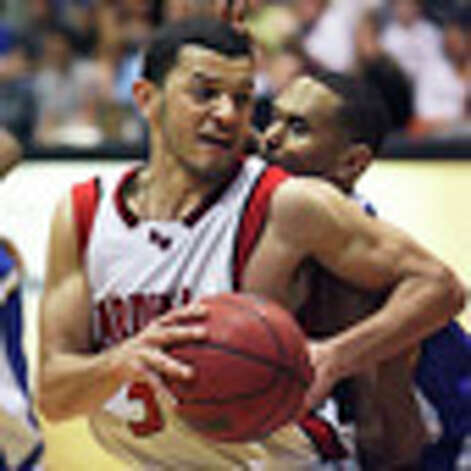 SPORTS   UIW's Pierce Caldwell is checked closely by Darren Lee as the University of the Incarnate Word plays St. Mary's at Greehey Arean for the Heartland Conference Championship on March 6, 2010.Tom Reel/Staff / © 2010 San Antonio Express-News