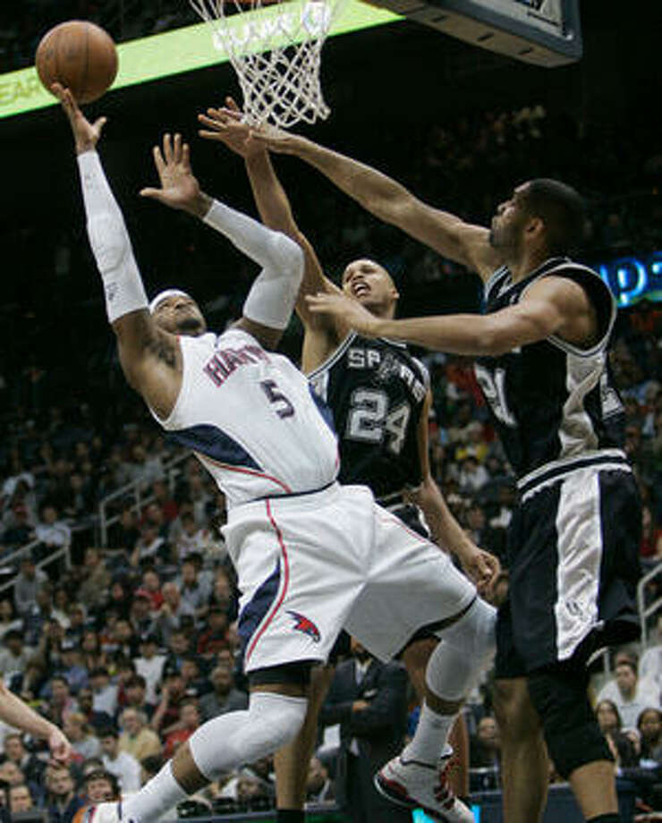 Atlanta Hawks forward Josh Smith (left) takes on the Spurs' Richard Jefferson (center) and Tim Duncan at the rim.