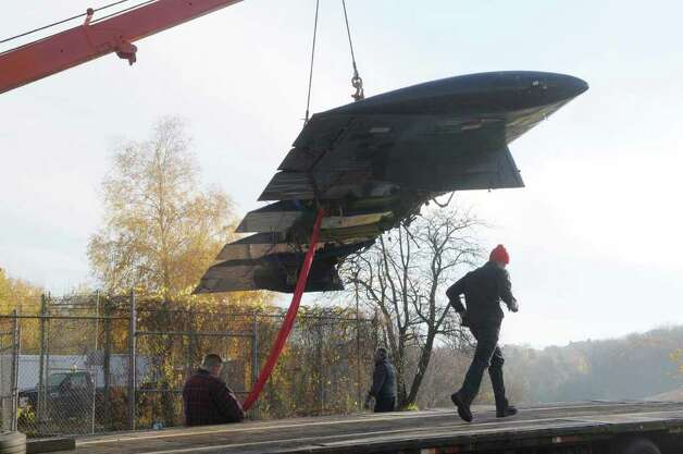 A section of the wing of a donated warplane is lifted by a heavy tow truck Wednesday at Questar III Rensselaer Educational Center in Troy.  (Paul Buckowski / Times Union) Photo: Paul Buckowski / 00010913A