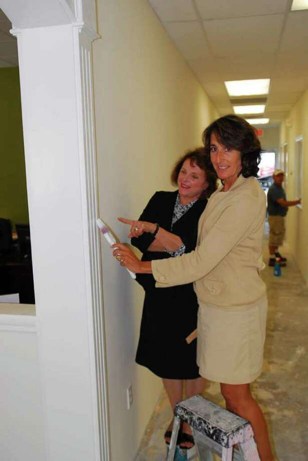 Pitching in to help put the finishing touches on Halstead Property's office expansion in Westport are, from left, agents Jean Coleman, of Weston, and Alison Sternberg, of Easton. Photo: Contributed Photo / Westport News contributed