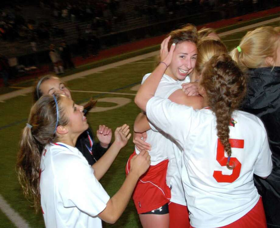 GAme MVP Alex DiStefano, right, is congratualted by her GHS teammates at the end of the 2010 Girls FCIAC Soccer Championship between Greenwich High School vs. Westhill High School at Norwalk High School, Wednesday night, Nov. 3, 2010.  Greenwich defeated Westhill, 1-0. Photo: Bob Luckey / Greenwich Time