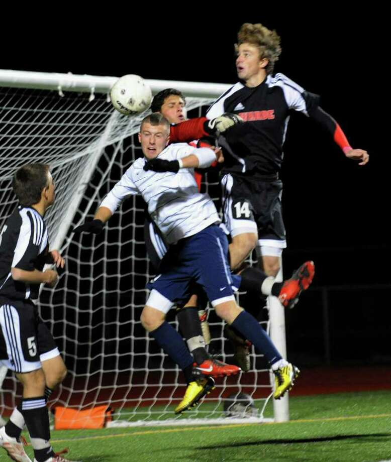Staples #9 Brendan Lesch tries to head the ball in for a goal but is hampered by Fairfield Warde goalie Dylan Strachen, top center, and #14 Connor Gavey, top right, during FCIAC Championship boys soccer in Norwalk, Conn. on Wednesday November 03, 2010. Photo: Christian Abraham / Connecticut Post