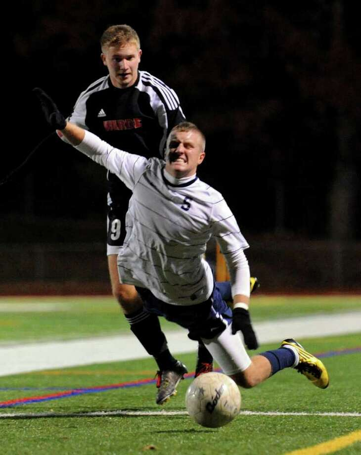 Staples #9 Brendan Lesch falls down after being tripped by Fairfield Warde's #9 Guthrie Carpenter, during FCIAC Championship boys soccer in Norwalk, Conn. on Wednesday November 03, 2010. Photo: Christian Abraham / Connecticut Post