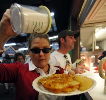 Kathy Ingram adds salt to her kartoffelpuffers. The German potato pancake, with a side of applesauce, is a New Braunfels tradition during the 10 days of Wurstfest.