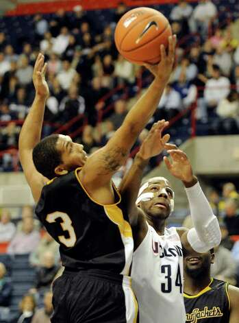 American International College's Isiah Wallace (3) grabs a rebound over Connecticut's Alex Oriakhi during the first half of their NCAA men's college basketball game in Storrs, Conn., on Wednesday, Nov. 3, 2010. Photo: Fred Beckham