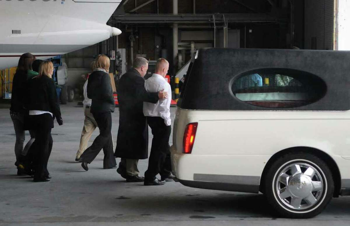 Family and friends walk past the hearse with the casket of Army Pfc. David Jones Jr. inside at a hangar at Griffiss International Airport in Rome, NY, during a military dignified transfer ceremony on Thursday, Nov. 4, 2010, for the body of Army Pfc. David Jones Jr. of St. Johnsville. Jones died from a gunshot wound Oct. 24 in Baghdad, Iraq. (Paul Buckowski / Times Union)