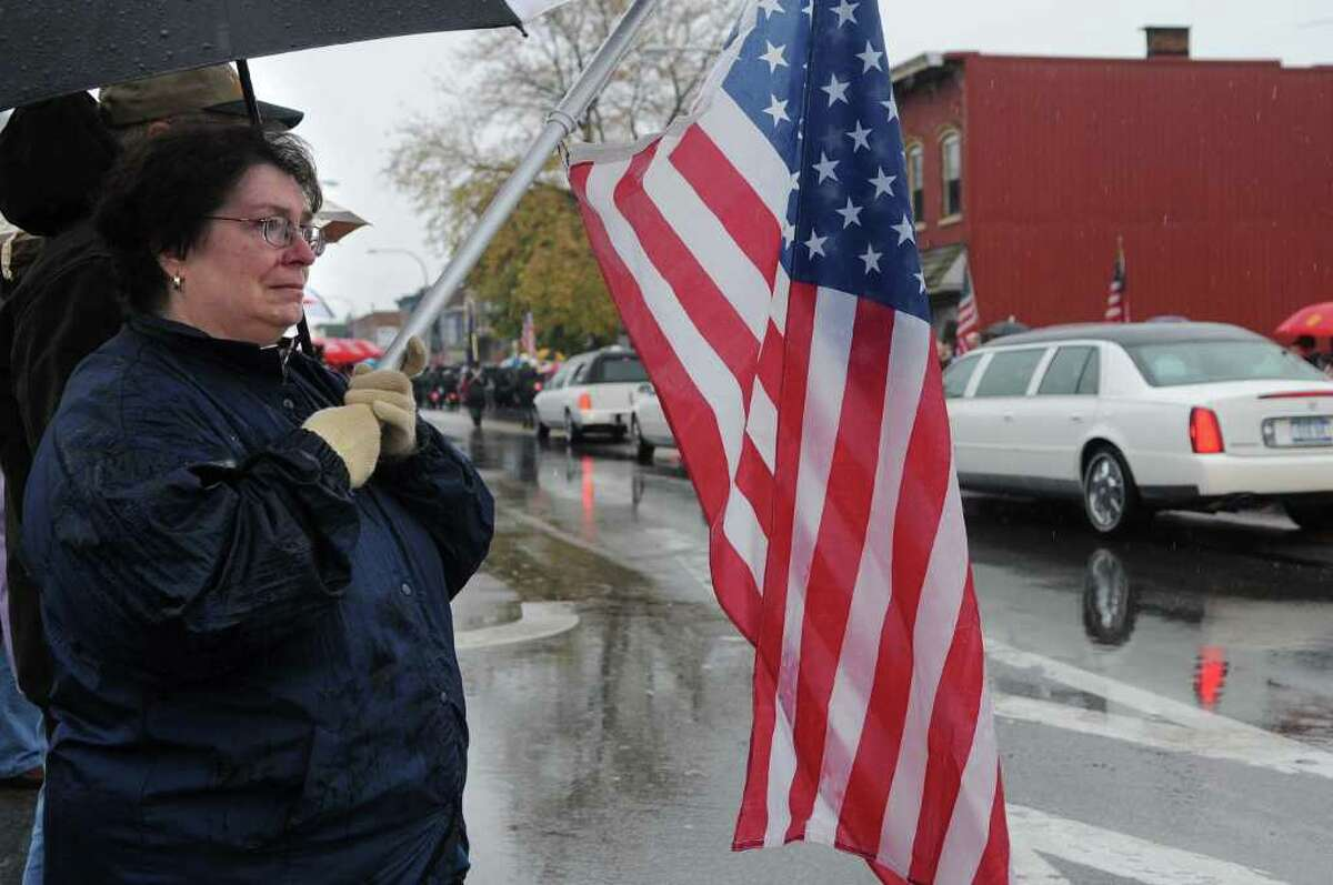 """Juanita Handy and Keith Handy from St. Johnsville stand on Main Street to pay their respects to Army Pfc. David Jones Jr. as the hearse carrying his body from Griffiss International Airport drove through town on Thursday, Nov. 4, 2010. Jones died from a gunshot wound Oct. 24 in Baghdad, Iraq. Juanita and Keith's son is in the Army and just finished his second tour in Iraq. """"We came out to pay our respects because you just don't know what it is like unless you have a child serving, and we are so grateful that our son is coming home to us alive,"""" Keith Handy said. (Paul Buckowski / Times Union)"""