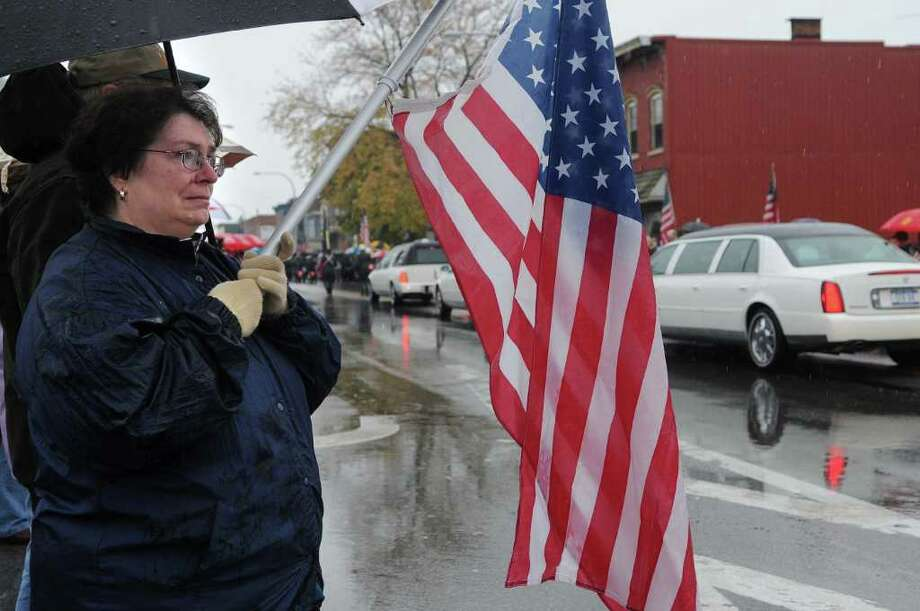 "Juanita Handy and Keith Handy from St. Johnsville stand on Main Street to  pay their respects to Army Pfc. David Jones Jr. as the hearse carrying his body from Griffiss International Airport drove through town on Thursday, Nov. 4, 2010.   Jones died from a gunshot wound Oct. 24 in Baghdad, Iraq.   Juanita and Keith's son is in the Army and just finished his second tour in Iraq.  ""We came out to pay our respects because you just don't know what it is like unless you have a child serving, and we are so grateful that our son is coming home to us alive,""  Keith Handy said.  (Paul Buckowski / Times Union) Photo: Paul Buckowski / 00010928A"