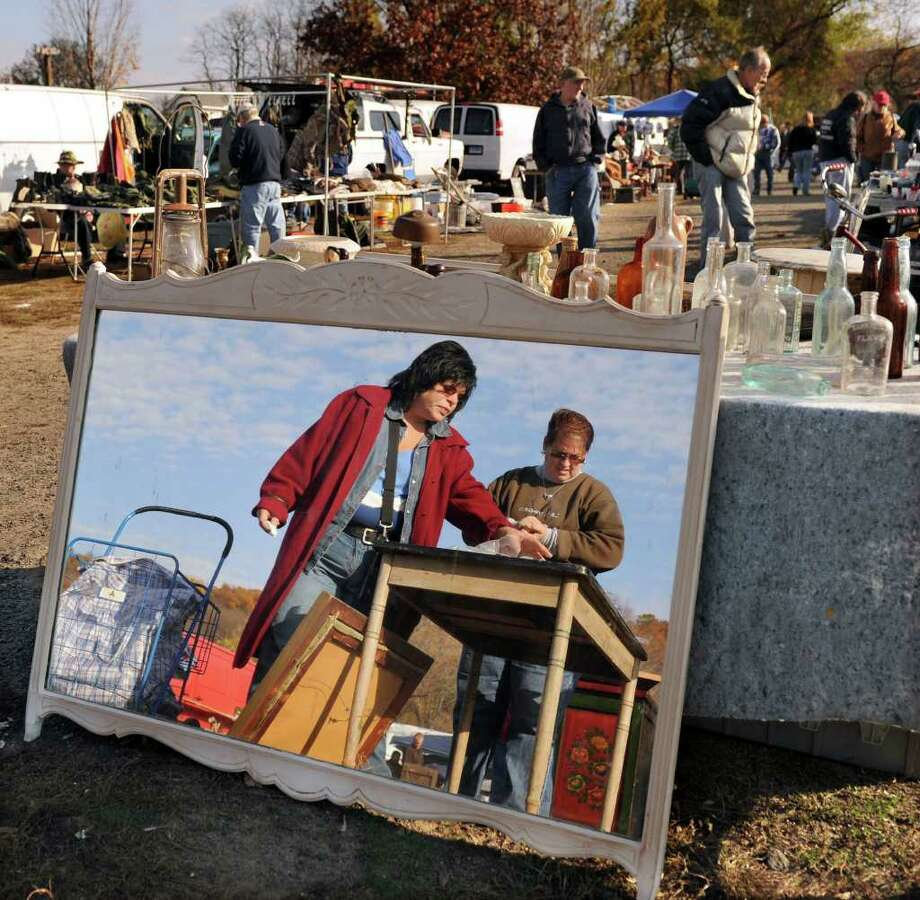 Cheryl Harlow of Wallingford, left, and  Donna Franco, right of West Haven are reflected in a mirror as they look at items at the Elephant's Trunk Country Flea Market Sunday, Oct. 31, 2010. Photo: Carol Kaliff / The News-Times