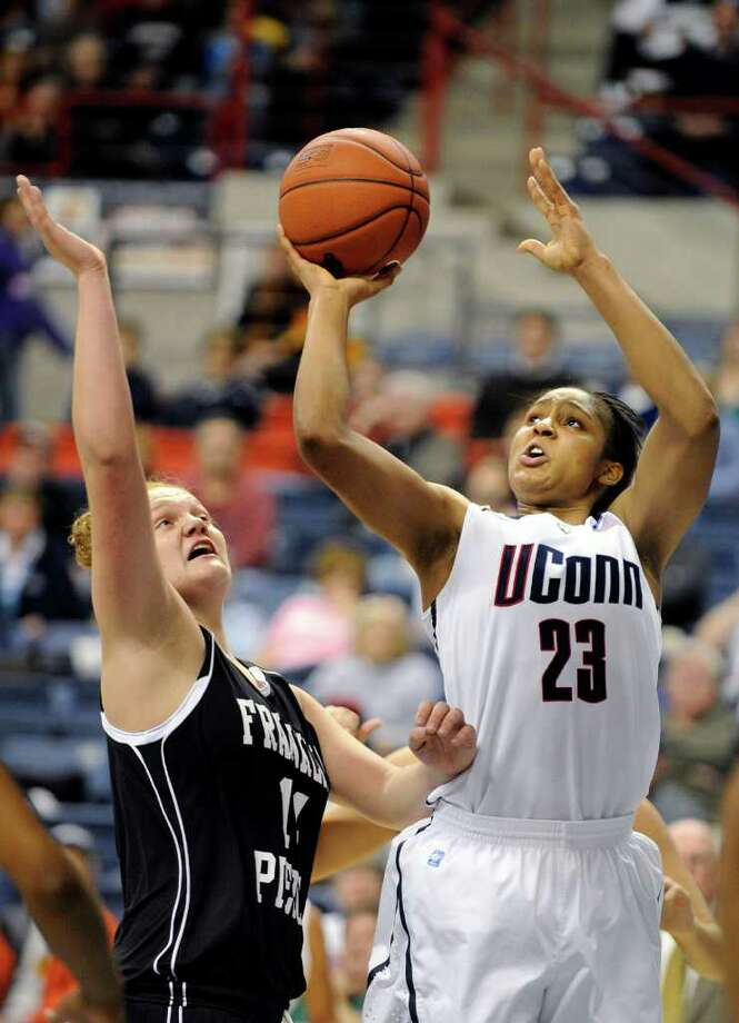 Connecticut's Maya Moore, right, drives to the hoop while being guarded by Franklin Pierce's Jessica Hurd during the first half of their exhibition NCAA women's college basketball game in Storrs, Conn., on Thursday, Nov. 4, 2010. (AP Photo/Fred Beckham) Photo: AP