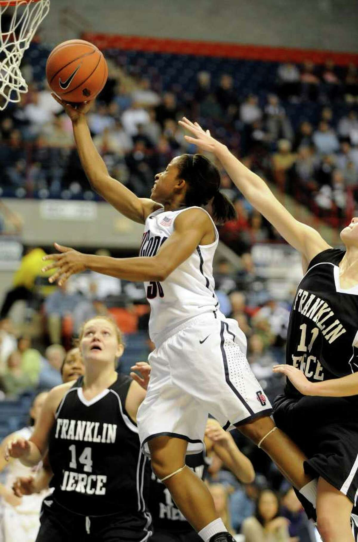 Connecticut's Lorin Dixon, center, drives past Franklin Pierce's Brooke Coderre (11) as Jessica Hurd (14) looks on during the second half of their exhibition NCAA women's college basketball game in Storrs, Conn., on Thursday, Nov. 4, 2010. Connecticut won the game 112-41. (AP Photo/Fred Beckham)