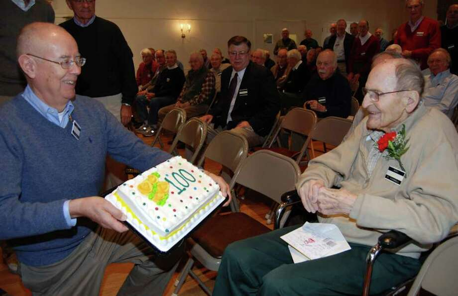 Marc Thorne presents a cake to Fred Farwell for his 100th birthday. Photo: Jeanna Petersen Shepard / Darien News