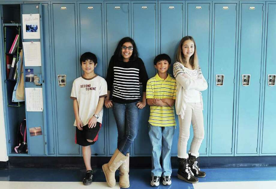 """Scofield Magnet Middle School students Richard Ira, Tanu Balla, Brian Niguidula and Nicole Smina have invented """"The Locker Stopper"""" as an entry in Liberty Science Center/TeleBrands Student Inventors Day.  The group stand by a row of lockers at the Scofield Magnet Middle School in Stamford, Conn. on Friday November 5, 2010. Photo: Kathleen O'Rourke / Stamford Advocate"""