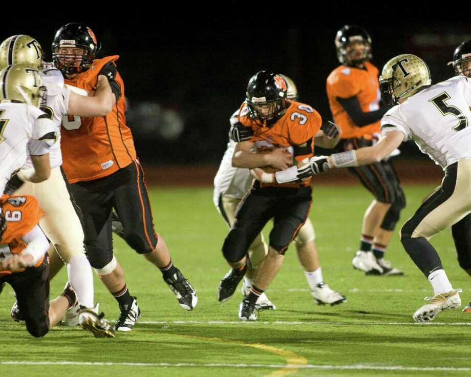 Ridgefield's Sam Gravitte (30) picks up yardage behind the blocking of Tommy Jordan during the Tigers' FCIAC game against Trumbull Friday night, Nov. 6, 2010, at Ridgefield High School. Photo: Barry Horn / The News-Times Freelance