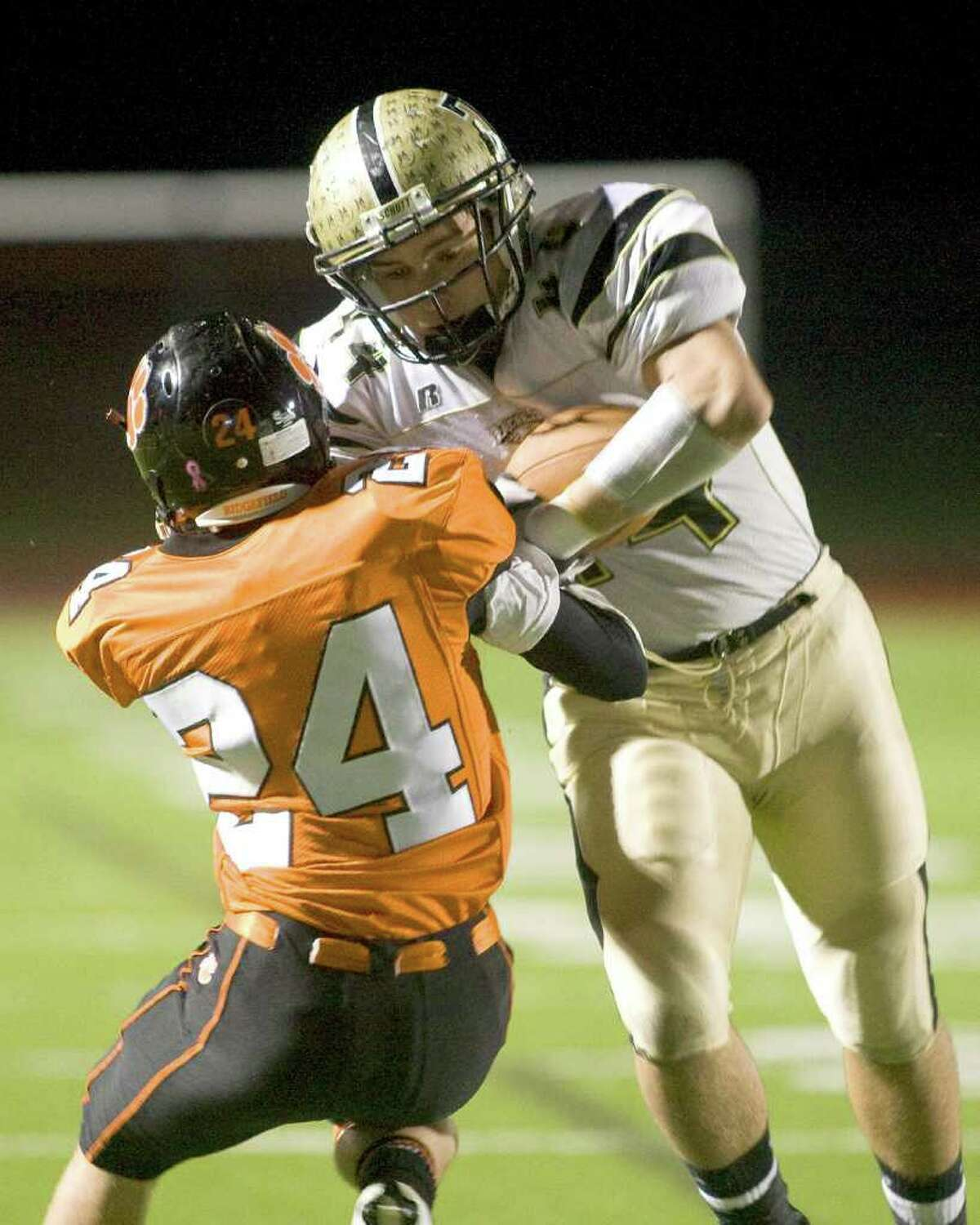 Trumbull's Don Cherry runs over Ridgefield's Stephen Gherardi (24) en route to a touchdown during their FCIAC game Friday night, Nov. 5, 2010, at Ridgefield High School.