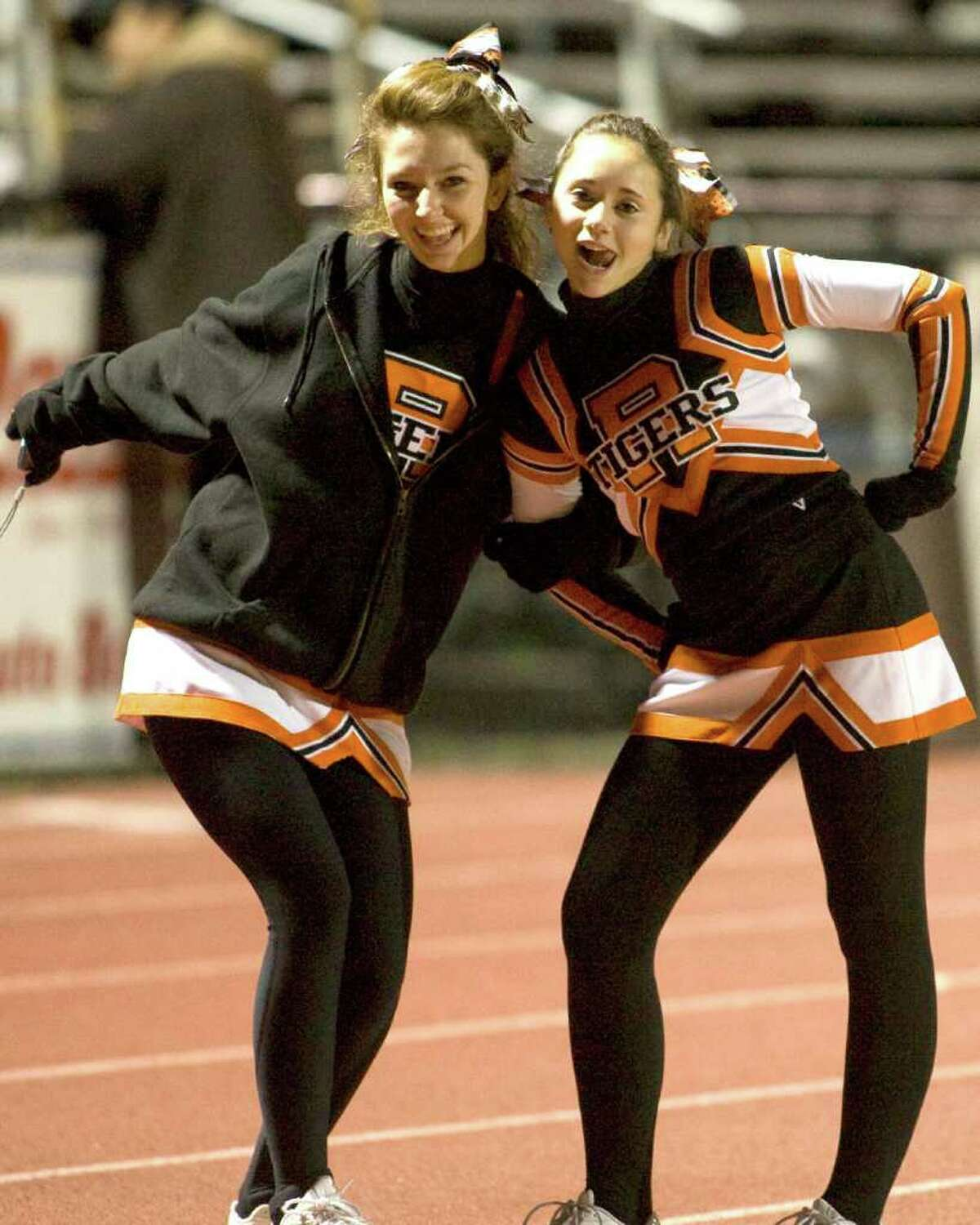 Two Ridgefield cheerleaders pose before the Tigers' football game against Trumbull Friday night, Nov. 5, 2010, at Ridgefield High School.