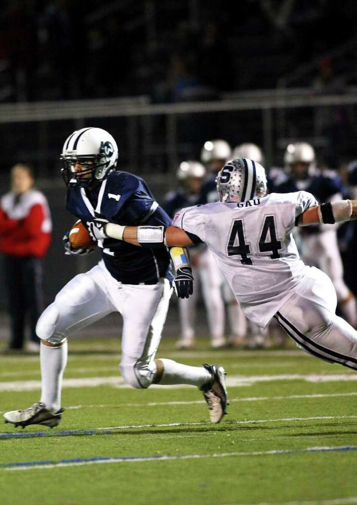 Robert Gau of Staples attempts to take down Matt Reyes of Wilton as the Wreckers play Wilton under the lights on Friday, November 5th in Wilton, Conn.