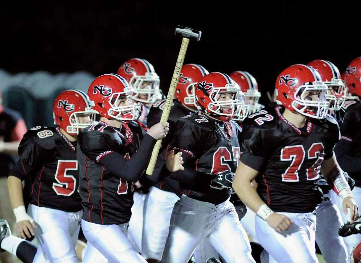 Ryan Shullman, # 11 of New Canaan High School carried the sledge hammer onto the field at the start of the High School football game between Greenwich High School vs. New Canaan High School at New Canaan High School, Friday night, Nov. 5, 2010.