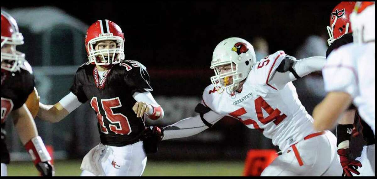 New Canaan's QB Matt Milano is pressured by Jim Barrett of GHS, right, during High School football game between Greenwich High School vs. New Canaan High School at New Canaan High School, Friday night, Nov. 5, 2010.