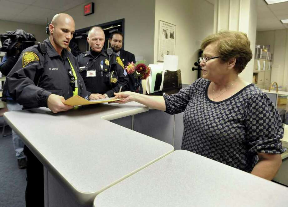 Bridgeport police deliver an envelope with head moderator returns from Bridgeport, Conn., to processing technician for Legislation and Elections Administration, Yolanda Santiago, right, at the Secretary of the State's office in Hartford, Conn., Friday, Nov. 5, 2010.  (AP Photo/Jessica Hill) Photo: Jessica Hill, AP / AP2010
