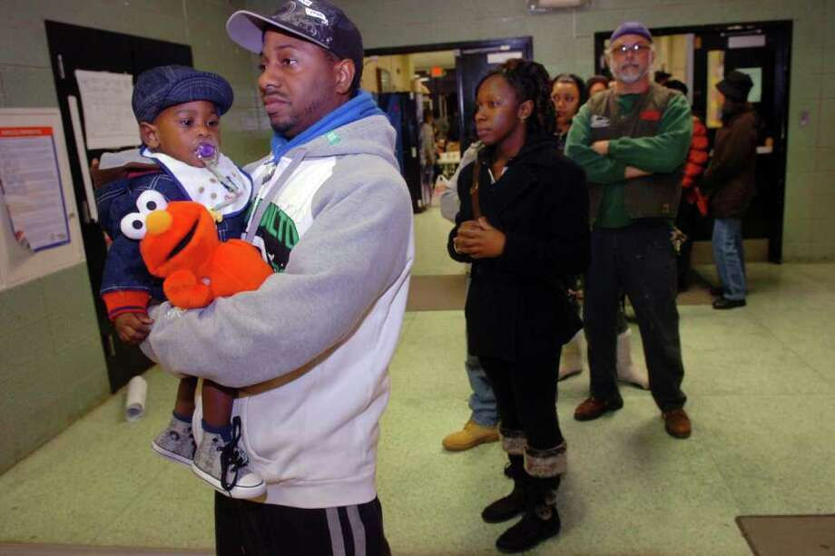 Vincent Campbell stands in line with his son Aiden, 1, as he waits to vote at Central High School, in Bridgeport, Conn. on election night, Nov. 2nd, 2010. Photo: Ned Gerard / Connecticut Post