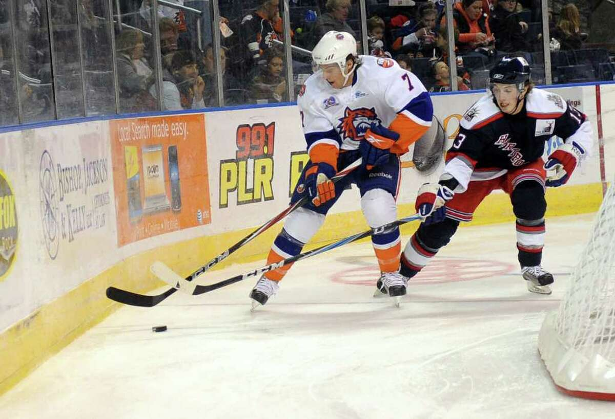 The Soundtigers' Tony Romano beats Hartford's Tim Kennedy for control of the puck and takes it around the net to score a goal for Bridgeport during Saturday's game against the Hartford Wolf Pack at the Arena at Harbor Yard on November 6, 2010.
