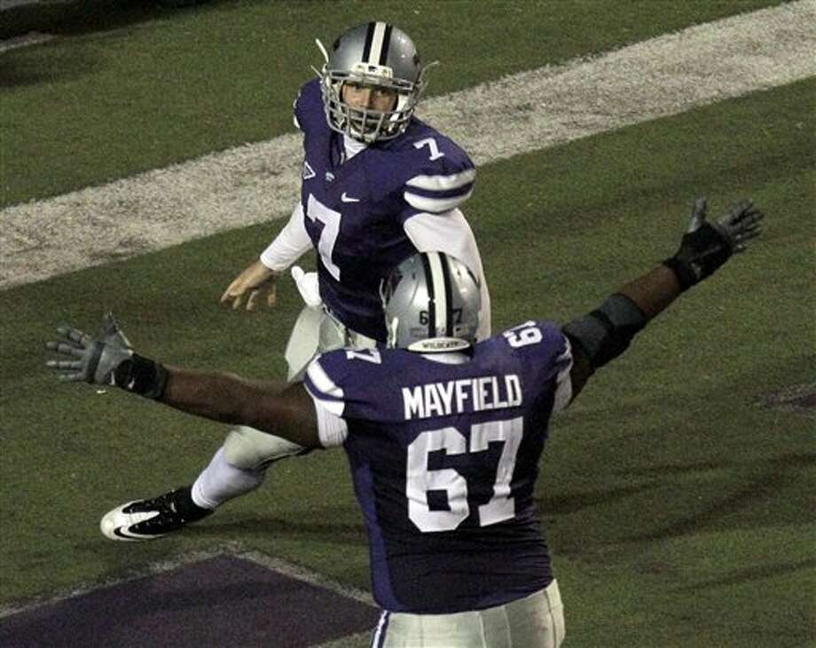 Kansas State quarterback Collin Klein (7) celebrates with offensive linesman Kenneth Mayfield (67) after scoring a second-quarter touchdown.