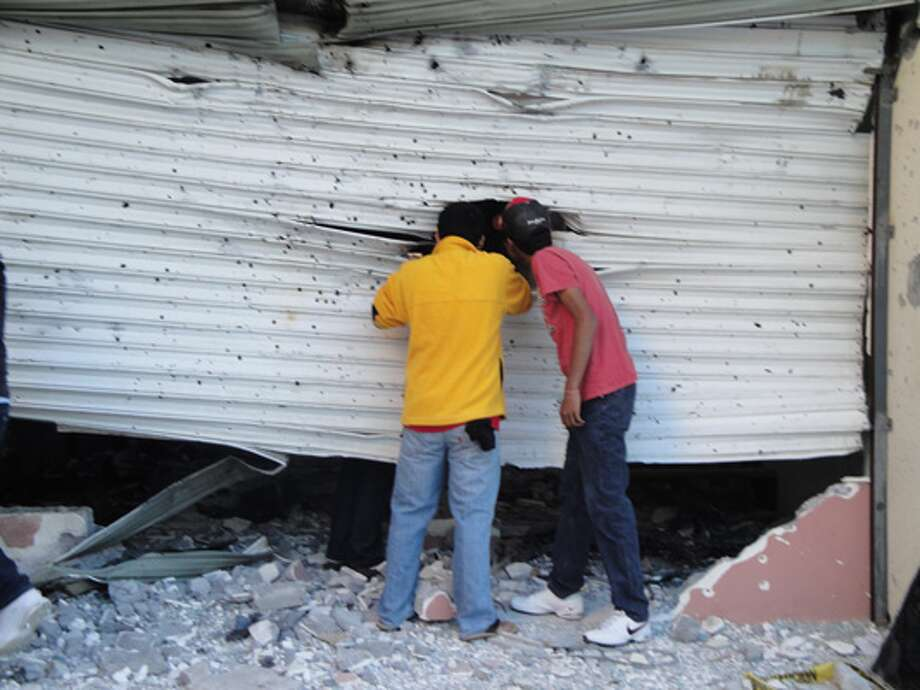 Residents cautiously look into an unused office building that was the scene of one of the gunbattles that rocked Matamoros, Mexico.