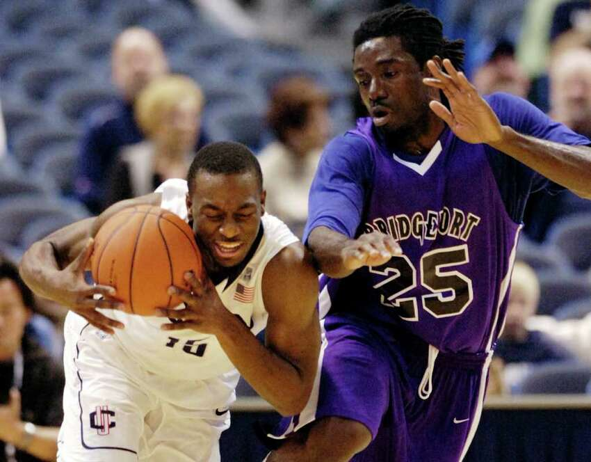 Connecticut's Kemba Walker, left, drives past Bridgeport's Msoo Ikyaator during the first half of Connecticut's 103-57 victory in an exhibition NCAA college basketball game in Hartford, Conn., on Sunday, Nov. 7, 2010. Walker scored a game-high 21 points and had eight rebounds. (AP Photo/Fred Beckham)