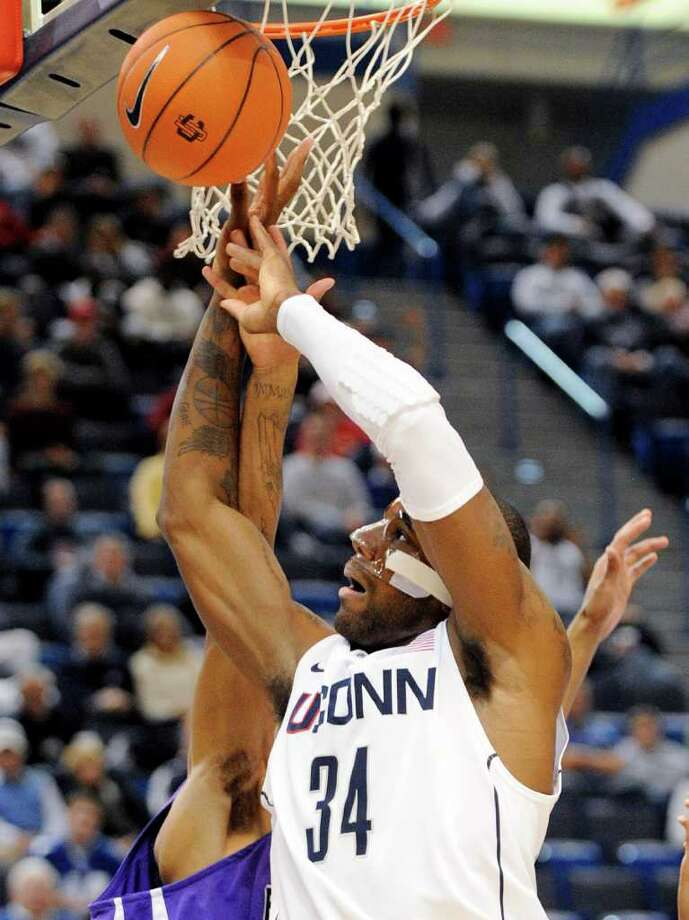 Connecticut's Alex Oriakhi is fouled by Bridgeport's Donte Mentor during the second half of Connecticut's 103-57 victory in an exhibition NCAA college basketball game in Hartford, Conn., on Sunday, Nov. 7, 2010. Oriakhi scored 16 points and had seven rebounds. (AP Photo/Fred Beckham) Photo: AP