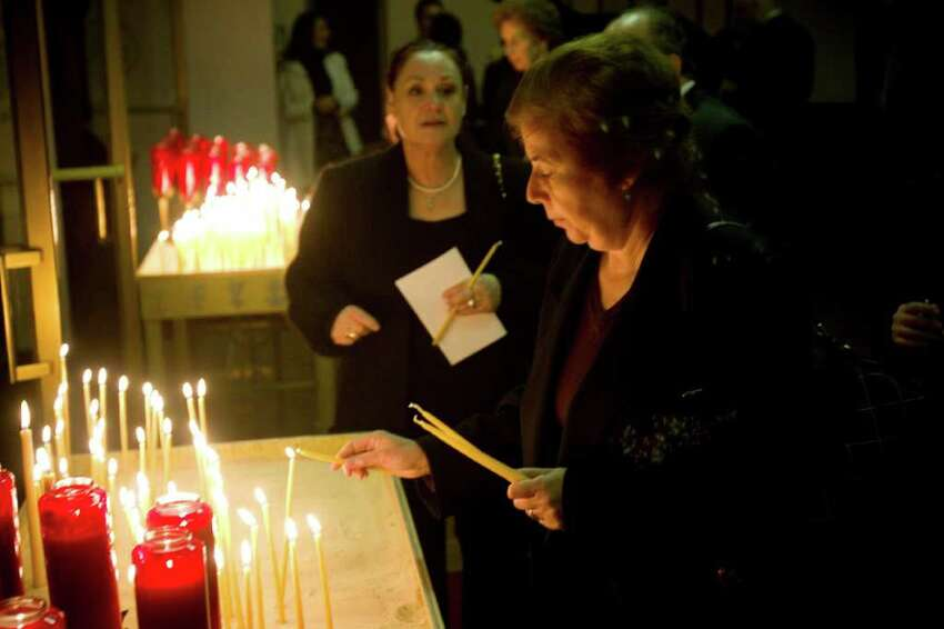 Parishoners lights candles before Archbishop Demetrios of America attended the name day vespers service at the Greek Orthodox Church of the Archangels in Stamford, Conn. on Sunday, Nov. 7, 2010.
