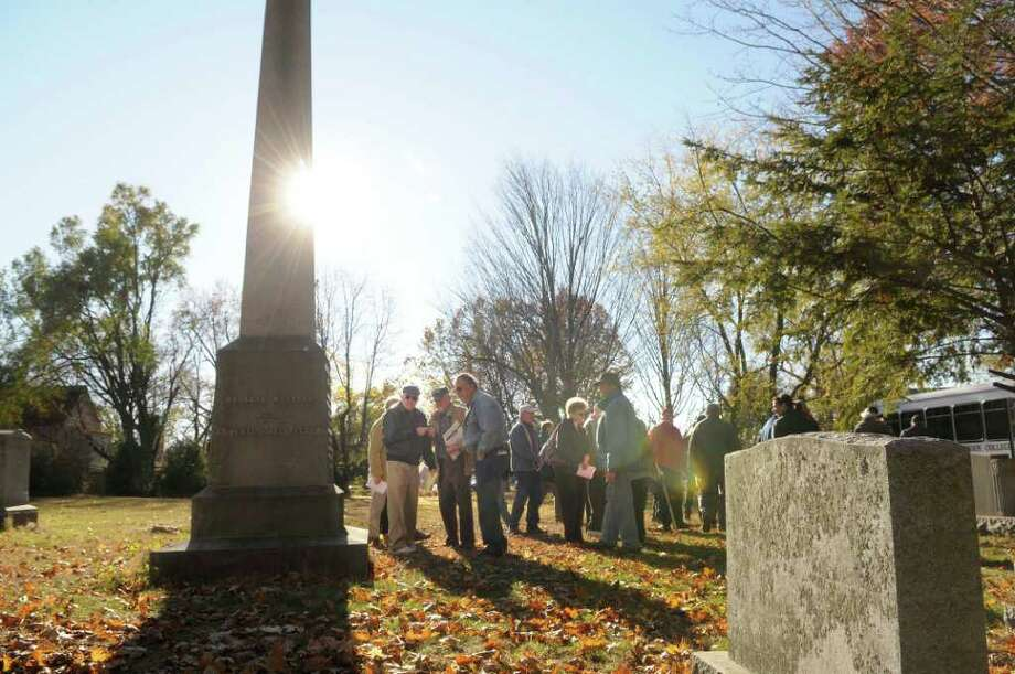 Siena College History Professor Tom Kelly, far left, leads a tour  during the Vale & Valor event at Vale Cemetery in Schenectady, on Sunday.  The grave Kelly is standing near is that of Ernest DeSpitzer, a German immigrant clergyman and physician, fought in the French and Indian War and became a Surgeon General of the Provincial Forces.  The Vale & Valor was a tour of the cemetery graves of soldiers who fought in the great military conflicts from 1775-1945.   The cemetery runs different tour programs from April to November each year.  (Paul Buckowski / Times Union) Photo: Paul Buckowski / 00010920A