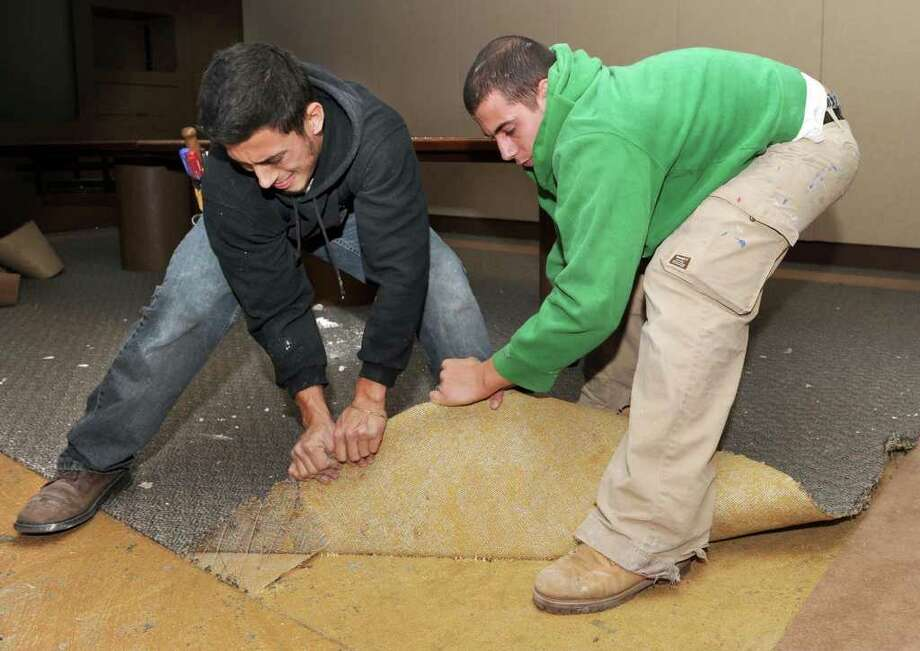 Carl Savino of Bethel, left, and A.J. Mota of Danbury, pull up carpet in office space that is being renovated for Guideposts at the Matrix Corporate Center in Danbury, Monday, Nov. 8, 2010. Photo: Carol Kaliff / The News-Times